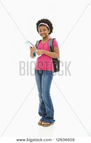 Chica afroamericana con libros y llevar mochila sonriendo al espectador.