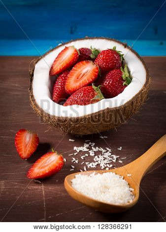 Half coconut with strawberries and shredded coconut on bright blue and brown rustic wooden background