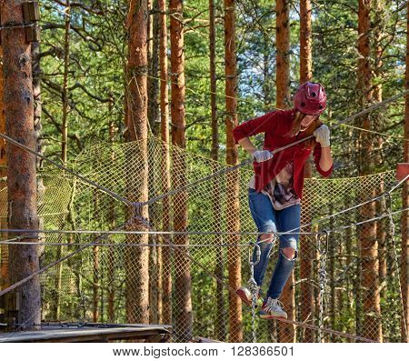 Girl passing through obstacles in a Forest Rope Park Challenge