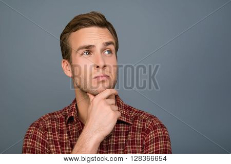 Young Handsome Ponder Man Dreaming On Gray Background