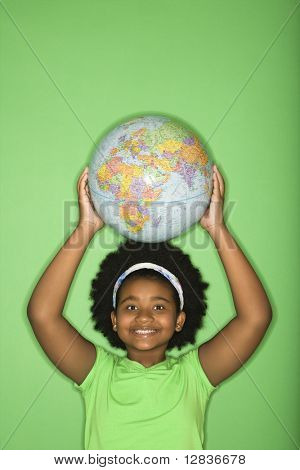 African American girl holding globe on top of head and smiling at viewer.