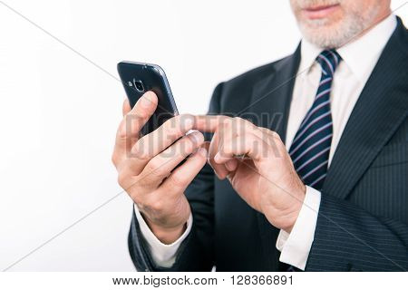 Close up photo of aged businessman typing message on his smartphone