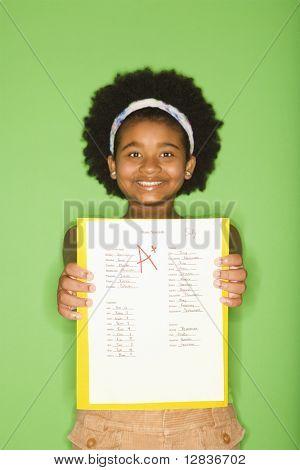 Chica afroamericana aguantando gradual asignación de escuela sonriendo orgullosamente en el espectador.