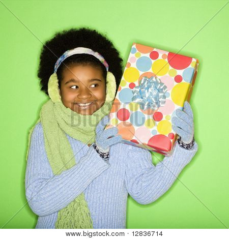 African American girl in winter clothing holding wrapped package.