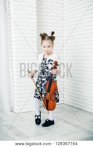 little girl with a violin showing tongue