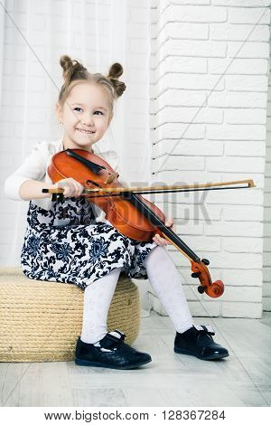 little girl sits holds a bow and smile language looking away