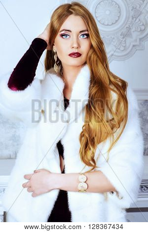 Elegant young woman in evening dress and mink fur jacket posing in vintage interior. Jewellery. Fashion shot.