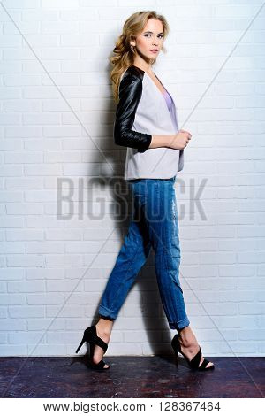 Fashion shot of a beautiful young woman in casual clothes standing by a white brick wall.