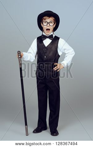 Elegant boy in a suit, bowler hat and glasses posing at studio with a walking stick. Children fashion.