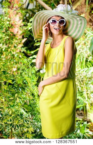 Romantic young woman in a beautiful hat and sunglasses in a blooming garden. Beauty, fashion.