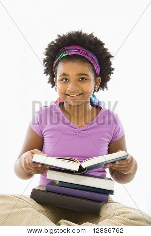 African American girl with large stack of books smiling at viewer.