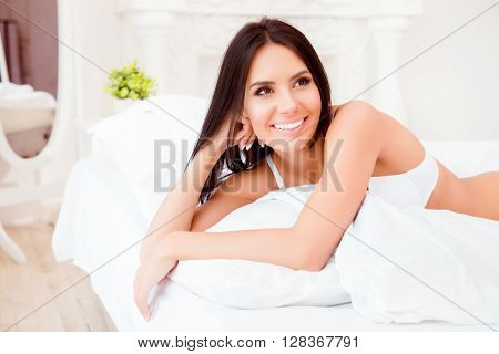 Portrait Of Cheerful Brunette Lying On Bed After Sleep