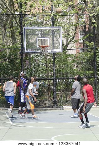 New-York City USA - May 04 2015: young men in action playing basket ball in the street