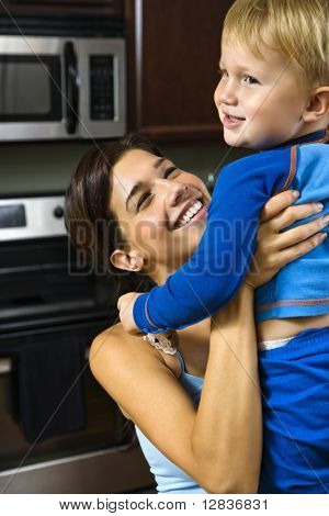 Caucasian woman in kitchen lifting smiling toddler son into the air.
