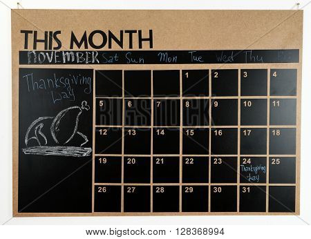 Chalkboard wall calendar with mark on 24 November