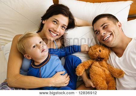 Caucasian Eltern und Kleinkind Sohn liegend im Bett zu Lächeln.