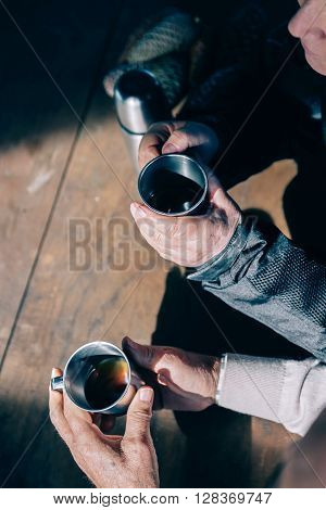 Top view of senior couple hands holding metal cups and drinking coffee over a wooden table