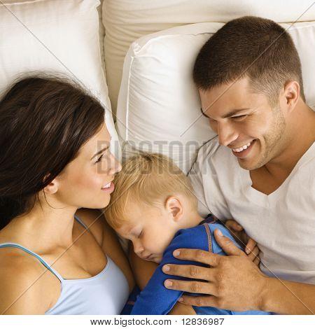 Caucásica mediados los padres adultos con hijo de niño durmiendo en la cama.