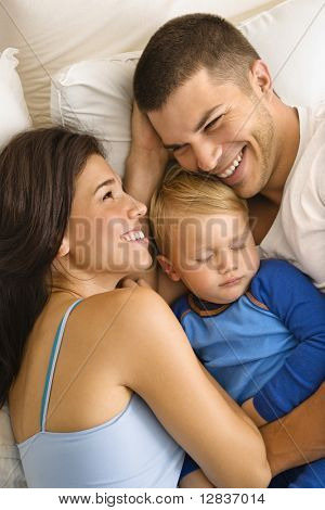 Caucasian mid adult parents cuddling with toddler son sleeping in bed.