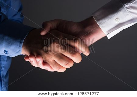Two Businessman Handshake Handshaking between darkness and light