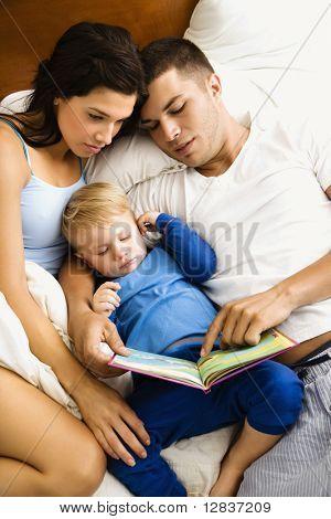 Caucasian Eltern und Kleinkind Sohn lesen Buch im Bett.
