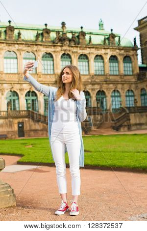 Woman tourist photographs the historic city center of Dresden, Germany