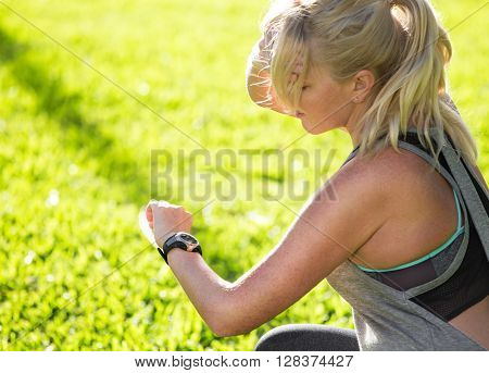 Female Athlete Looking At Heart Rate Monitor. Holding Forehead And Tracking Her Activities