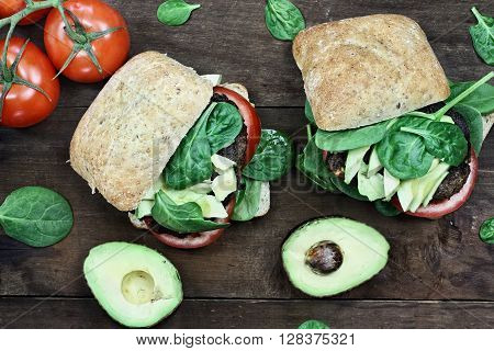 Vegetarian hamburger made from ground mushrooms with avocados tomatoes and spinach taken from above. Dairy and meat free.