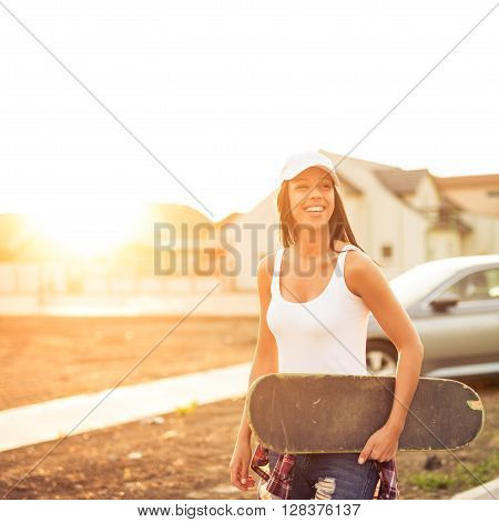 Woman enjoying skating outdoors on the sunset.