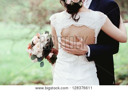 The bride and groom arm in arm amid the natural greenery. The hands of the newlyweds together. Wedding Couple. ** Note: Visible grain at 100%, best at smaller sizes