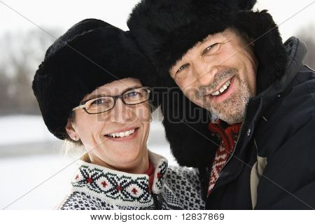 Portrait of happy Caucasian middle aged man and woman in winter clothing and black hats looking at viewer smiling.