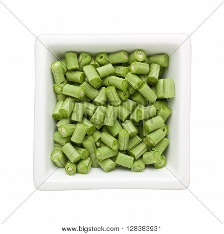 Chopped long beans in a square bowl isolated on white background