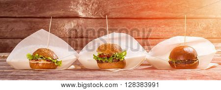 Burgers on paper wrappers. Different hamburgers on wooden background. Selection of burgers in bistro. Variety of recipes.