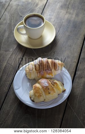Coffee and croissant for breakfast on rustic wooden table top view