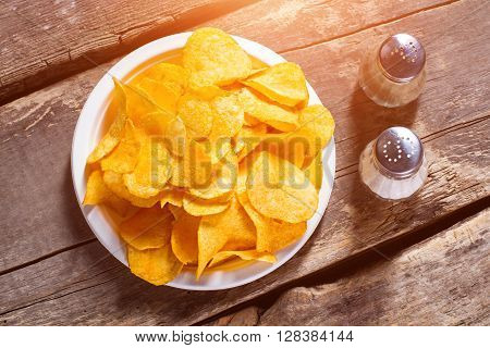 Chips with salt and pepperbox. Pepperbox and chips on table. Simple recipe of potato chips. Popular junk food and spices.