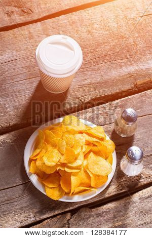 Chips and hot drink cup. Drink and chips on table. Hot coffee and crispy food. Morning snack in retro cafe.
