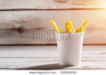 French fries in a cup. Fries on white wooden background. Size of portion in cafe. Free snack for bistro clients.