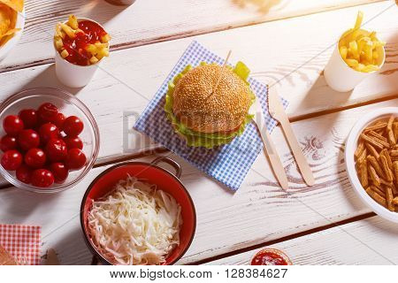 Burger with cutlery and tomatoes. Fries, sauerkraut and burger. Food set served at bistro. Hearty breakfast idea.