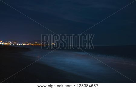 Night scape of the sea coast. Beach in the darkness, city lights at the horizon. Alanya, Turkey, Mediterranen region