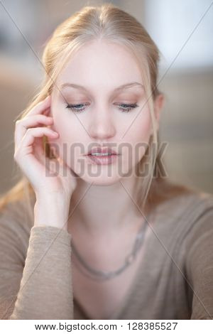 Portrait of thoughtful young woman looking down.