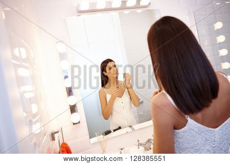 Young woman applying lip gloss in mirror at bathroom.
