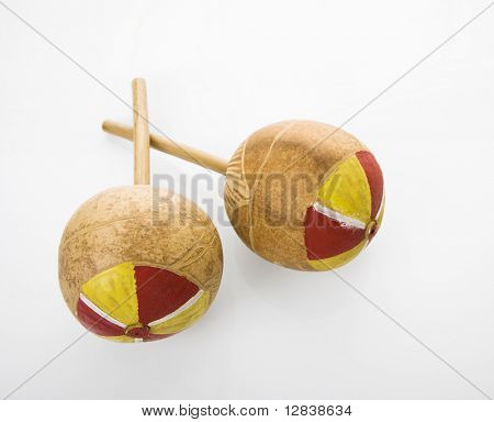 Pair of handmade Mexican maracas percussion musical instruments against white background.