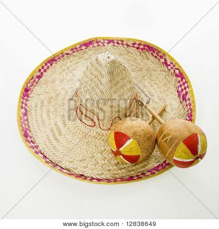 Par de instrumentos musicales de percusión de maracas mexicanas a mano en el sombrero del sombrero de paja.