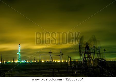Oil pump jack and drilling rig at the night sky background. Long exposure.