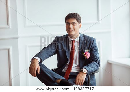 Gorgeous smiling groom looking at camera. Handsome man in a suite with a buttonhole sitting on chair against white wall indoors