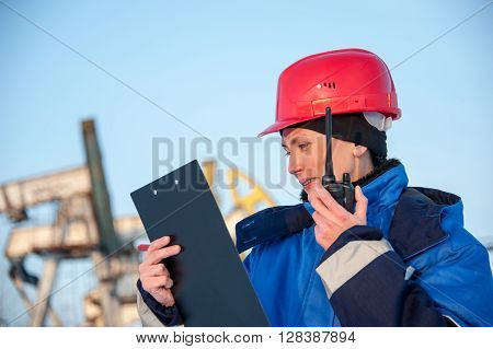 Female worker in the oil field talking on the radio wearing red helmet and blue work clothes. Industrial site background.