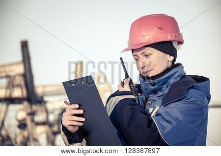 Female worker in the oil field talking on the radio wearing red helmet and blue work clothes. Industrial site background. Toned.