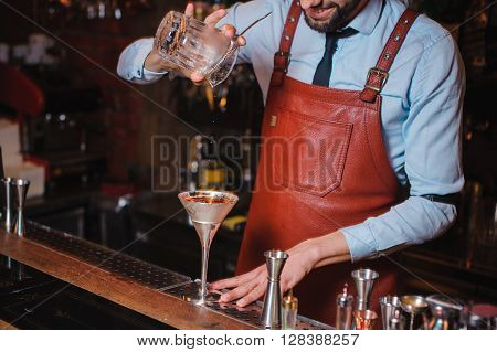 bartender pouring a cocktail into glass close-up. no face