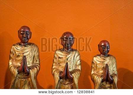 Three wooden statues of Buddhist disciples against orange wall.