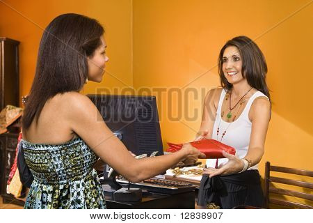African American women handing item to sales clerk in boutique.